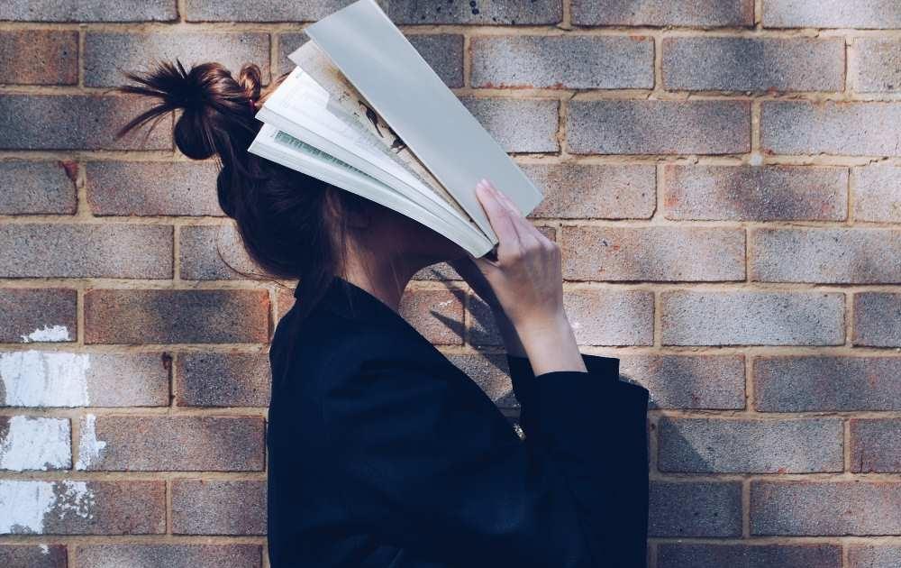 jeune femme avec un livre préparant le baccalauréat